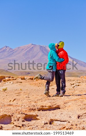 Bolivia, Antiplano - couple of tourists kissing with volcano Ollague in background - stock photo
