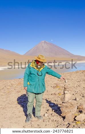 Bolivia, Antiplano - senior tourist watches cairn (Quechuan shrine ).  Laguna Verde and Licancabur volcano in background, Eduardo Avaroa Andean Fauna National Reserve, Sur Lipez, Bolivia - stock photo