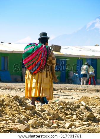 Bolivian woman - cholita - with colorful canvas sack, typical colorful clothes and hut walking on the street of El Alto, Bolivia. View from back. - stock photo