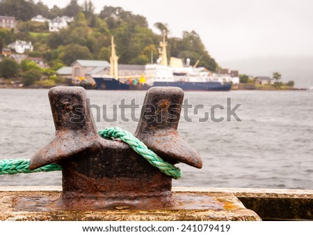 bollard with green rope in oban harbour - stock photo