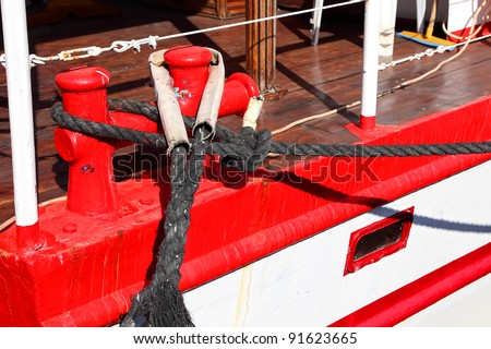 Bollards with black rope on the desk of red yacht (Eilat, Israel) - stock photo