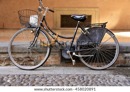 BOLOGNA, ITALY - APRIL 21, 2016: Old bicycle standing on a background of ancient urban architecture.
