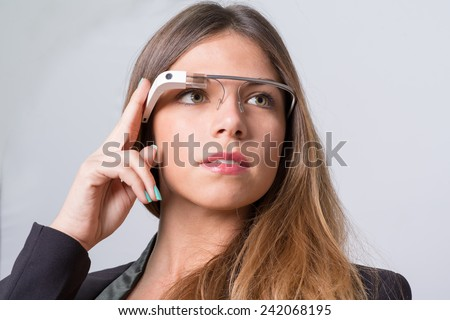 Bologna, ITALY - Jan 4, 2015: A woman wearing Google Glass. Google Glass is a wearable computer with an optical head-mounted display that is being developed by Google - stock photo