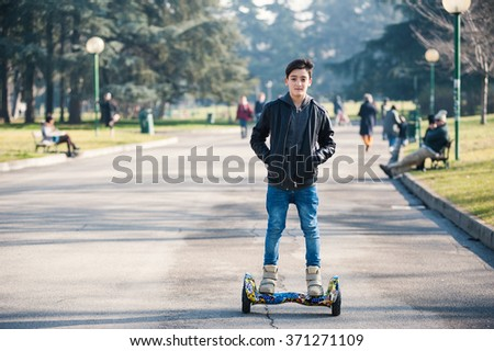 BOLOGNA, ITALY -  JANUARY 31, 2016: Teenager on Hoverboard, a rechargeable battery-powered scooter. It consists of two wheels arranged side-by-side, with two small platforms between the wheels. - stock photo