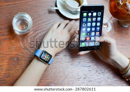 BOLOGNA, ITALY - June 12, 2015:  One girl wears the apple watch while using the iphone 6. - stock photo