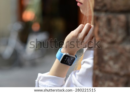 BOLOGNA, ITALY - MAY 17, 2015: One girl wears the apple watch with blurred urban background - stock photo