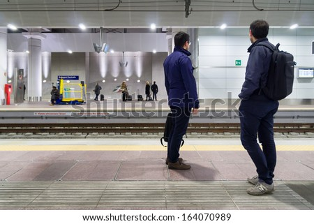 BOLOGNA - NOVEMBER 22: Commuters waiting high speed trains in central station, a brand new and very modern train stations. Bologna, Italy, November 22, 2013. - stock photo