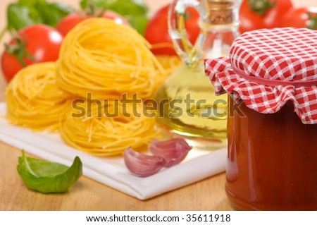 Bolognaise sauce in a jar with pasta, tomatoes and basil - stock photo