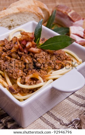 Bolognesa Pasta with bacon and bread on a handmade mat