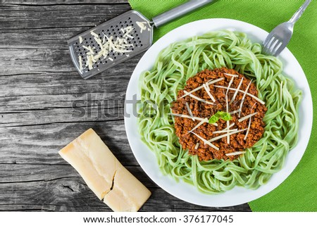 Bolognese ragout with green  pasta tagliatelle on a white plate, decorated with basil leaves, authentic recipe, wooden background parmesan cheese, top view - stock photo