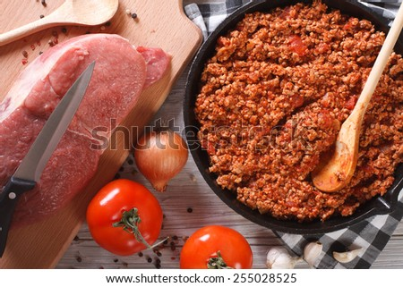 Bolognese sauce in a skillet with the ingredients on the table. horizontal view from above closeup