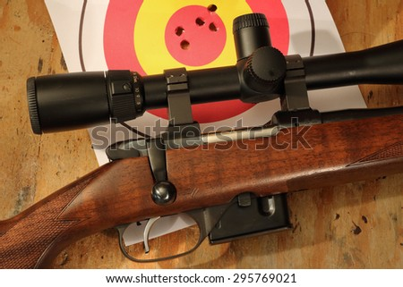 bolt action rifle with target and bullet holes - stock photo