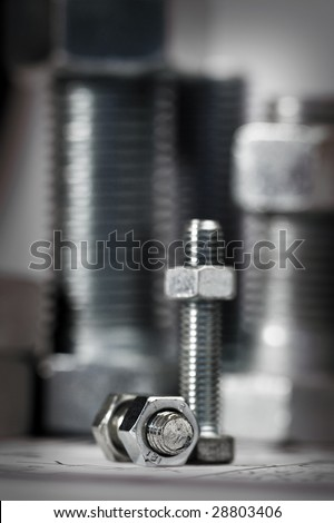 bolt and nut over big bolts,shallow dof - stock photo