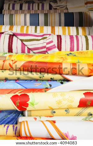Bolts of colorful fabrics ready for sale at a market. - stock photo