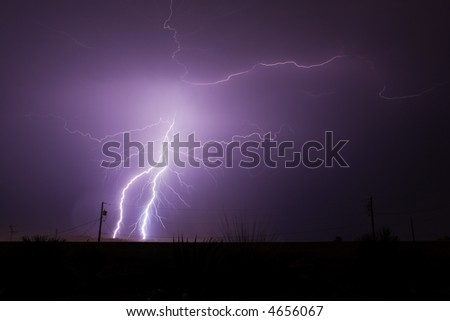 Bolts of lightning strike and splinter off during a monsoon rain storm in the Arizona desert.