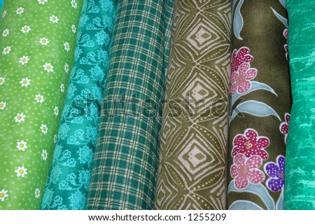Bolts of quilt fabric in the green range. - stock photo