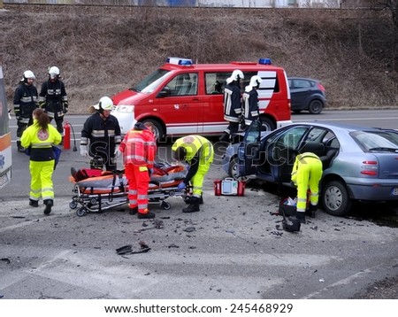 BOLZANO BOZEN, ITALY - JANUARY 20, 2015: Paramedics and Fireman provide first aid to injured motorist after hard collision between two cars on the iced road in winter time on January 20, 2015. - stock photo