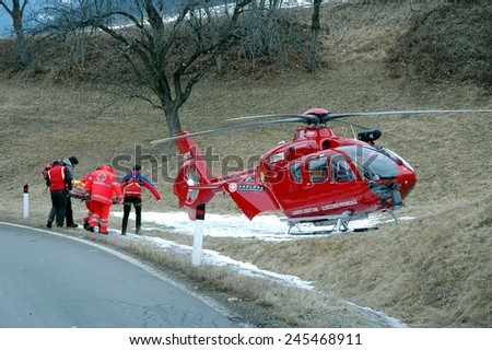 BOLZANO BOZEN, ITALY - JANUARY 20, 2015: Paramedics and helicopter pilot carry a injured motorist to hospital after a car crash collision between two cars on the iced road on January 20, 2015. - stock photo