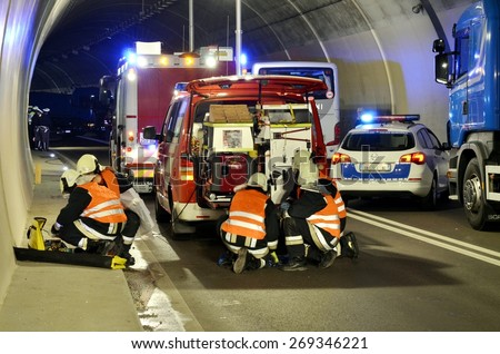 BOLZANO, ITALY - APRIL 5, 2015: Firefighters and paramedics at work after hard collision in a freeway gallery between two cars in Bolzano on April 5, 2015 - stock photo