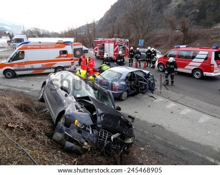 BOLZANO, ITALY - JANUARY 20, 2015: Paramedics and Firemen provide first aid to injured motorist after hard collision between two cars on the iced road in winter time on January 20, 2015. - stock photo