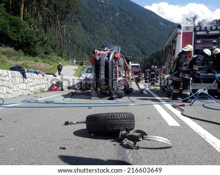 BOLZANO, ITALY - JULY 5, 2014: Firefighters at work after collision between two cars on the road. Car crash turned upside-down in Bolzano on July 5, 2014 - stock photo