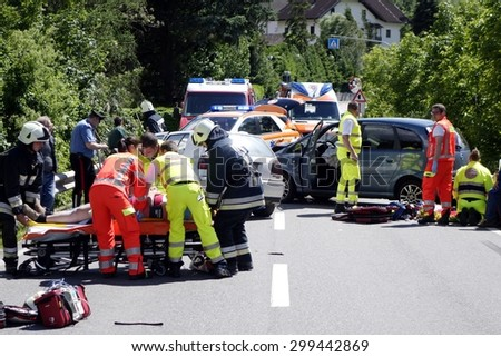 BOLZANO, ITALY - JULY 24, 2015: Paramedics and Firemen provide first aid to injured motorist after hard collision between two cars on the road in summer time on July 24, 2015. - stock photo