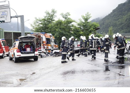 BOLZANO, ITALY - July 28, 2014: Paramedics Firefighters and police man working after a huge car crash collision. Closed road after car accident with injured motorist on the road on July 28, 2014. - stock photo