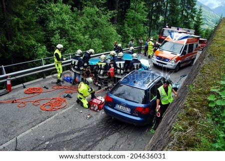 BOLZANO, ITALY - Juny 6, 2013: Paramedics Firefighters and police man working after a huge frontal car crash accident with injured motorist on the road on Juny 6, 2013 - stock photo