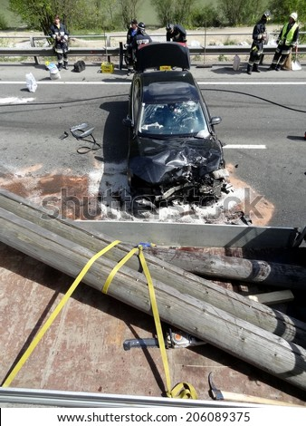 BOLZANO, ITALY - MAY 6, 2013: Fatal motorbike car crash accident after a  frontal collision between two cars on the road with intervention of paramedics and firefighters on May 6, 2013 - stock photo