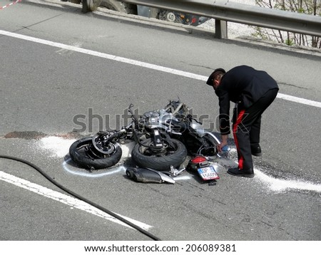 BOLZANO, ITALY - MAY 6, 2013: Fatal motorbike car crash accident after a  frontal collision between two cars on the road with intervention of paramedics, carabinieri and firefighters on May 6, 2013 - stock photo