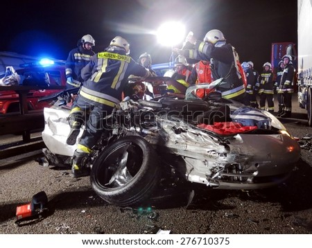 BOLZANO, ITALY - MAY 11, 2015: Firefighters and Paramedic at work after hard collision between car and truck on the freeway. Fatal accident with Porsche car came under a truck on May 11,2015. - stock photo