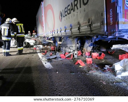 BOLZANO, ITALY - MAY 11, 2015: Firefighters at work in the night after hard collision between car and truck on the freeway. Fatal accident with car came under a truck on May 11,2015. - stock photo