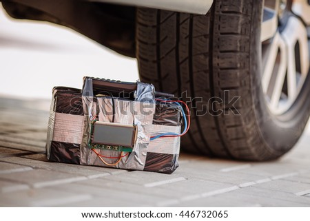 bomb with radio control and digital countdown timer at the wheel of the car. terrorism concept - stock photo