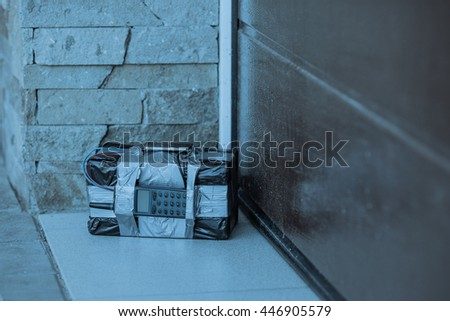bomb with radio control and digital countdown timer bomb near the garage door. terrorism and dangerous life concept - stock photo