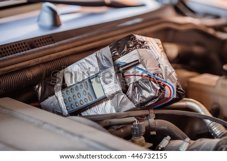 bomb with radio control and digital countdown timer on a car engine. terrorism and dangerous life concept - stock photo