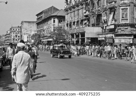 BOMBAY, INDIA - FEBRUARY 15, 1984: traffic and crowd of people in the city main street. The place is every day extremely crowded. - stock photo