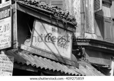 BOMBAY, INDIA - FEBRUARY 15, 1984: very old advertising in the city main street. Advertising panels are very typical all along the street. - stock photo