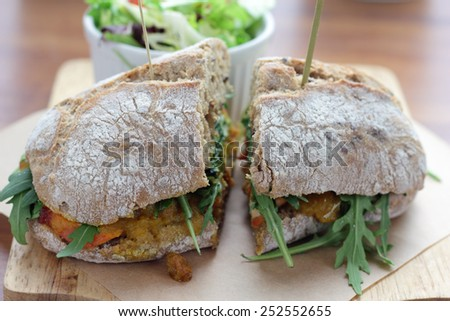 Bombay masala sandwich with chicken, rocket and green salad. - stock photo