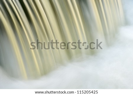 Bond falls cascade captured by motion blur and illuminated by reflected color from sunlit autumn trees, Michigan's Upper Peninsula. - stock photo