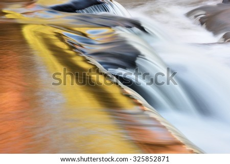 Bond Falls cascade captured with motion blur and illuminated by reflected color from sunlit autumn foliage and blue sky overhead, Michigan's Upper Peninsula, USA - stock photo