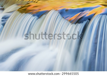 Bond Falls cascade illuminated with reflected color form sunlit autumn foliage, and blue sky overhead, Michigan's Upper Peninsula, USA - stock photo