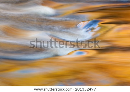 Bond Falls rapids captured with motion blur and illuminated by reflected color from sunlit autumn maples and blue sky overhead, Michigan's Upper Peninsula, USA  - stock photo