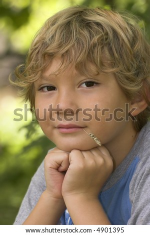 Bond haired boy chewing on a straw.