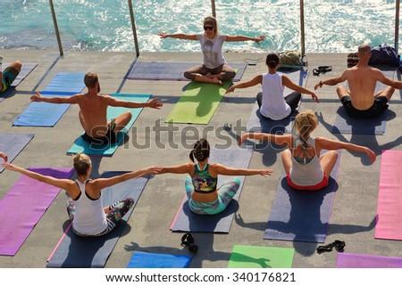 BONDI, AUSTRALIA- OCTOBER 25, 2015;  Yoga by the beach Bondi.   Yoga class beside the pool at Bondi Icebergs, Bondi Australia.  Participants perform yoga moves outdoors by the sea.  - stock photo
