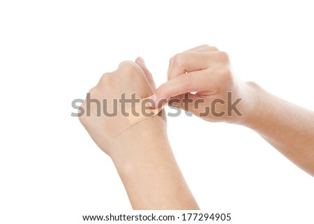 Bonding medicated plaster on woman's hand, isolated on a white background.