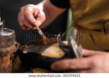 Bonding shoes.Shoemaker performs shoes in the studio craft - stock photo