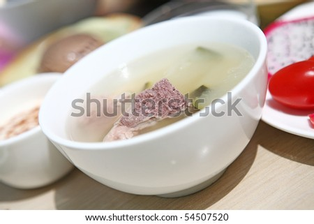 bone soup in a white bowl on table - stock photo