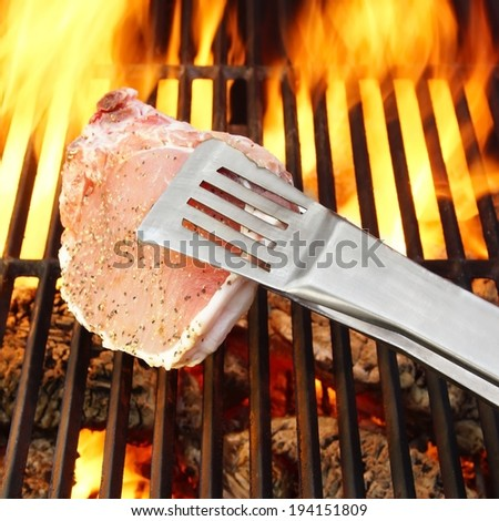 Bone steak held tongs over a hot grill and flames in the background, you can also see more pictures of BBQ in my set - stock photo