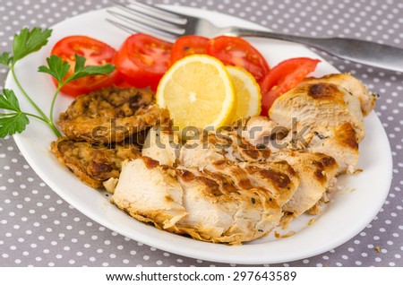 Boneless breast of chicken seasoned with rosemary and lemon and grilled to golden brown.  Served with fried green tomatoes and vine ripened tomatoes. - stock photo