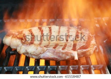 Boneless Rib-eye steak cooking on a barbecue with flames and smoke - stock photo